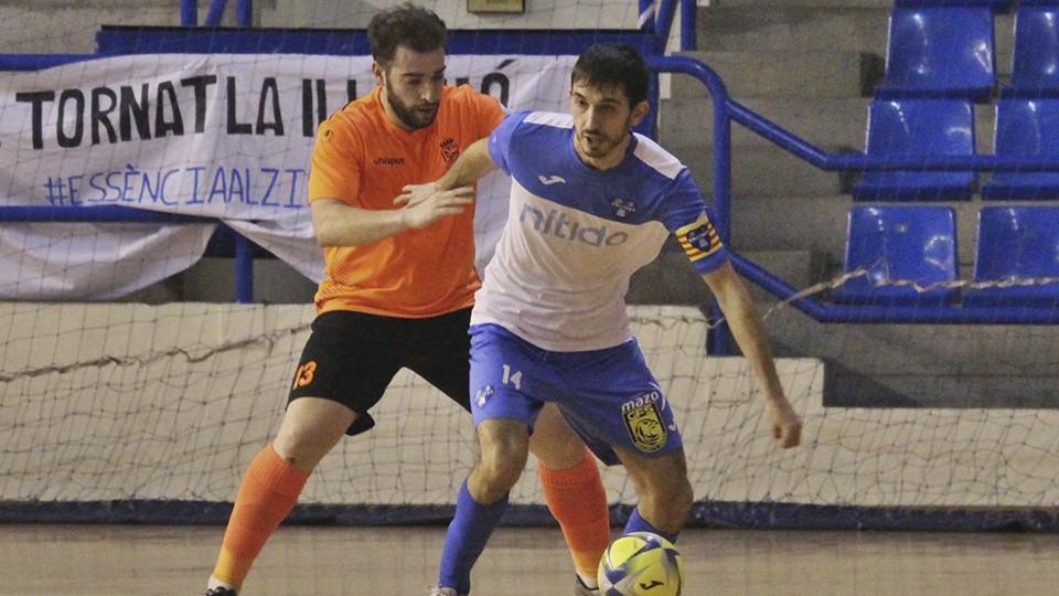 Xavi, jugador del Nítida Alzira, protege el balón ante Jorge Salcedo, del Ciudad de Móstoles.