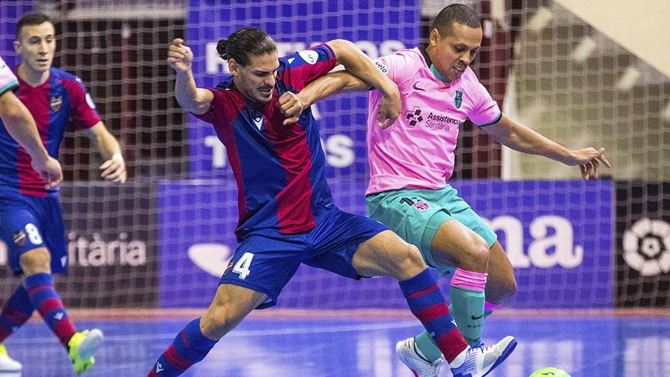 Esteban, jugador del Levante UD FS, pugna por el balón con Ferrao, del Barça.