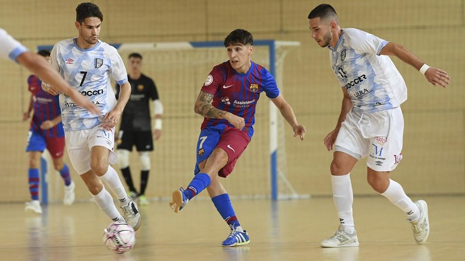 Álex García, de Barça B, pasa el balón entre dos rivales.